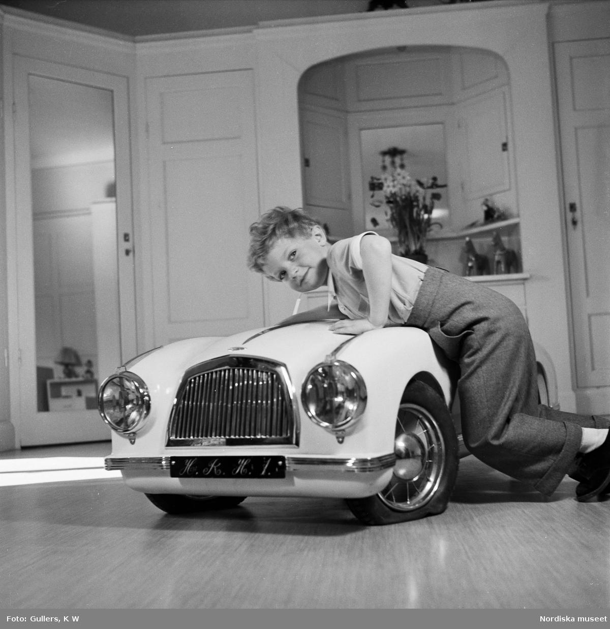 Kronprins Carl Gustaf leker med en trampbil. På nummerplåten