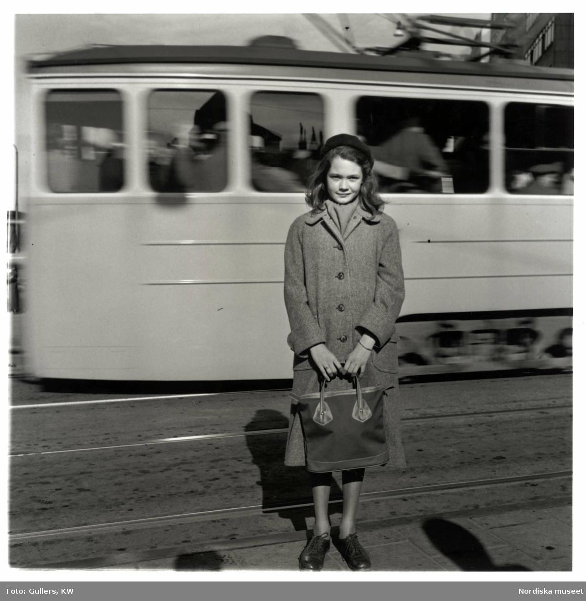 Flicka med väska framför spårvagn. Norrköping, modereportage för tidningen Vi.