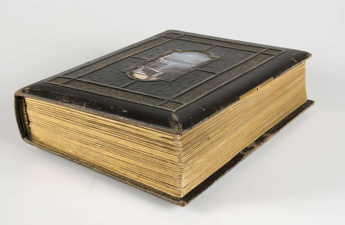 Fotoalbum med pärmar av svart läder och dekor i relief och guldtryck. På framsidans pärm finns en mittspegel av glas på vilket ett landskapsmotiv i månsken är målat. På baksidans pärm finns fyra nitar av metall.