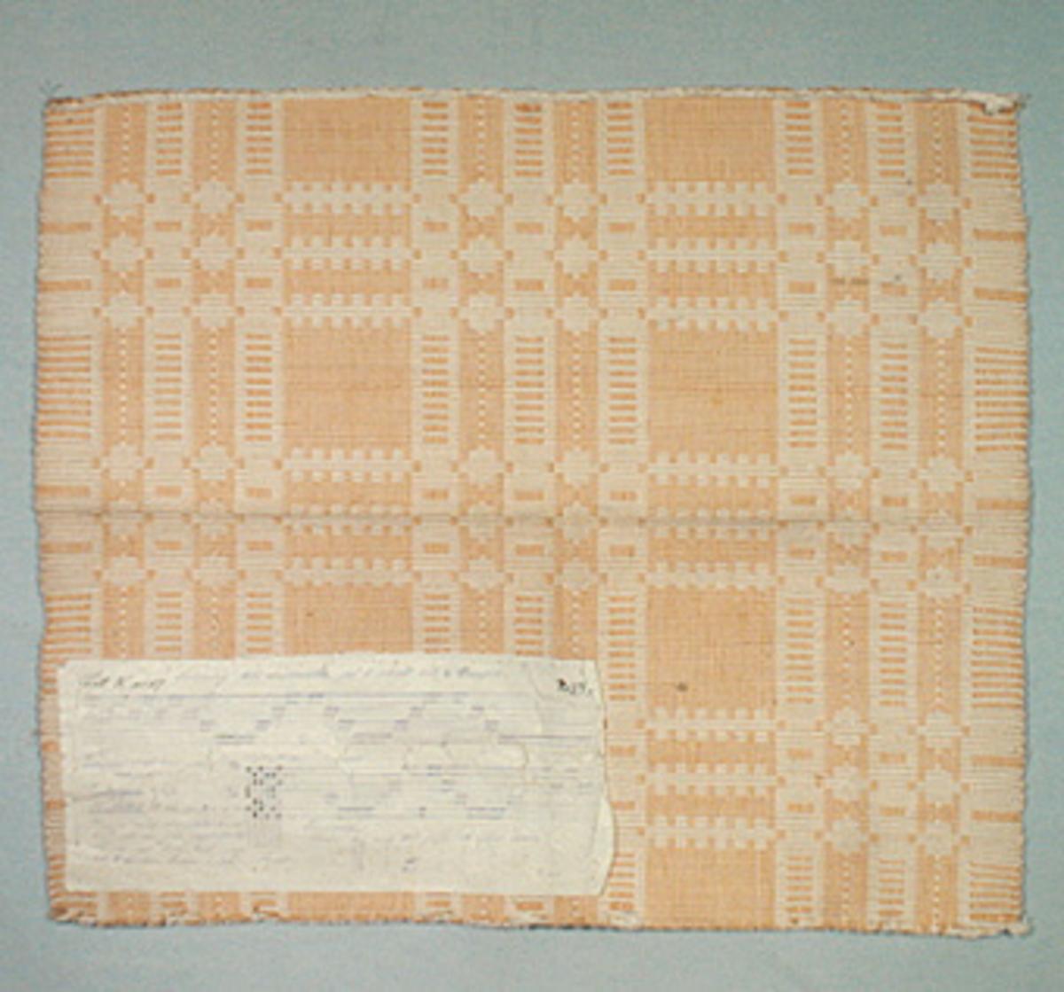 Vävprov ämnat som matta, vävt med bomullsgarn i både varp och inslag. Vävtekniken är rips och färgerna är vitt och gult. På mattan finns en vaxad tyglapp med vävinformation. Mattprovet är märkt B119.