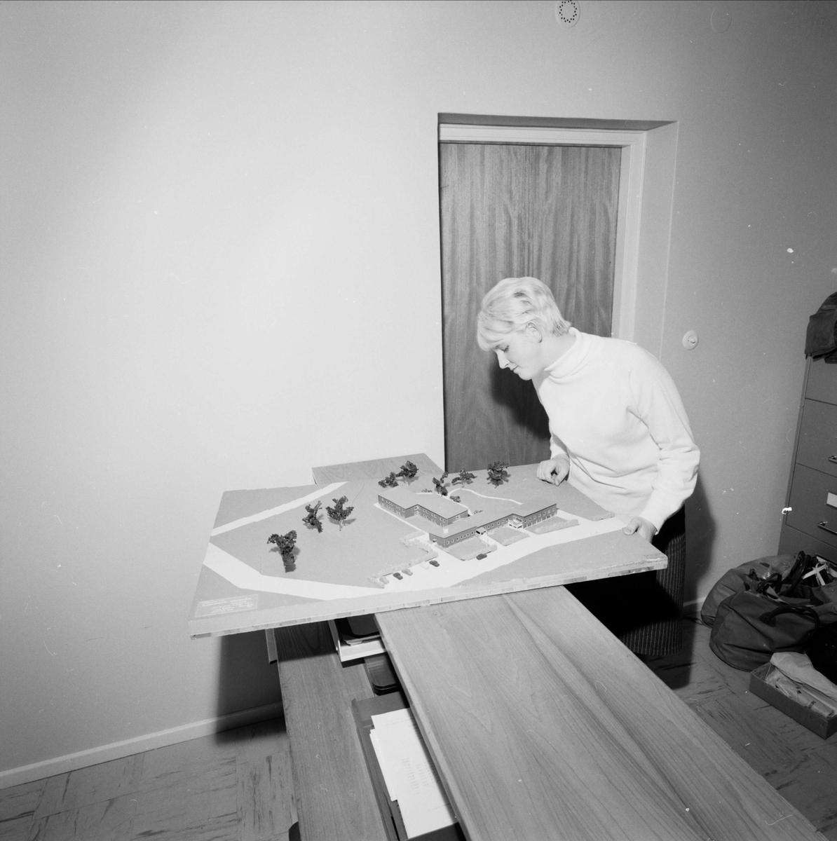 En kvinna tittar på modell över bebyggelse i Morgongåva, Vittinge socken, Uppland