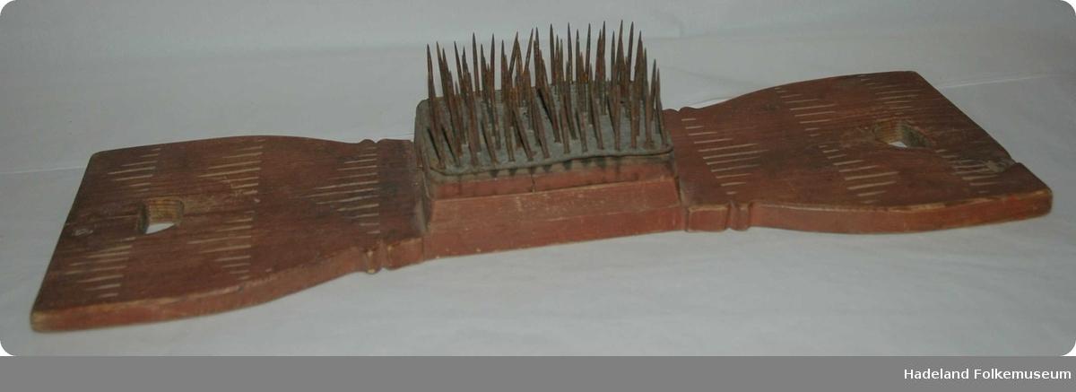 Rektangulær treplate som er noe innsnevret på midten. Et hull i hver ende fungerer som håndtak. Midt på platen er det to mindre rektangulære trestykker som danner base for en firekantet metallplate med jernpigger som står opp. Utskjært X+staver.