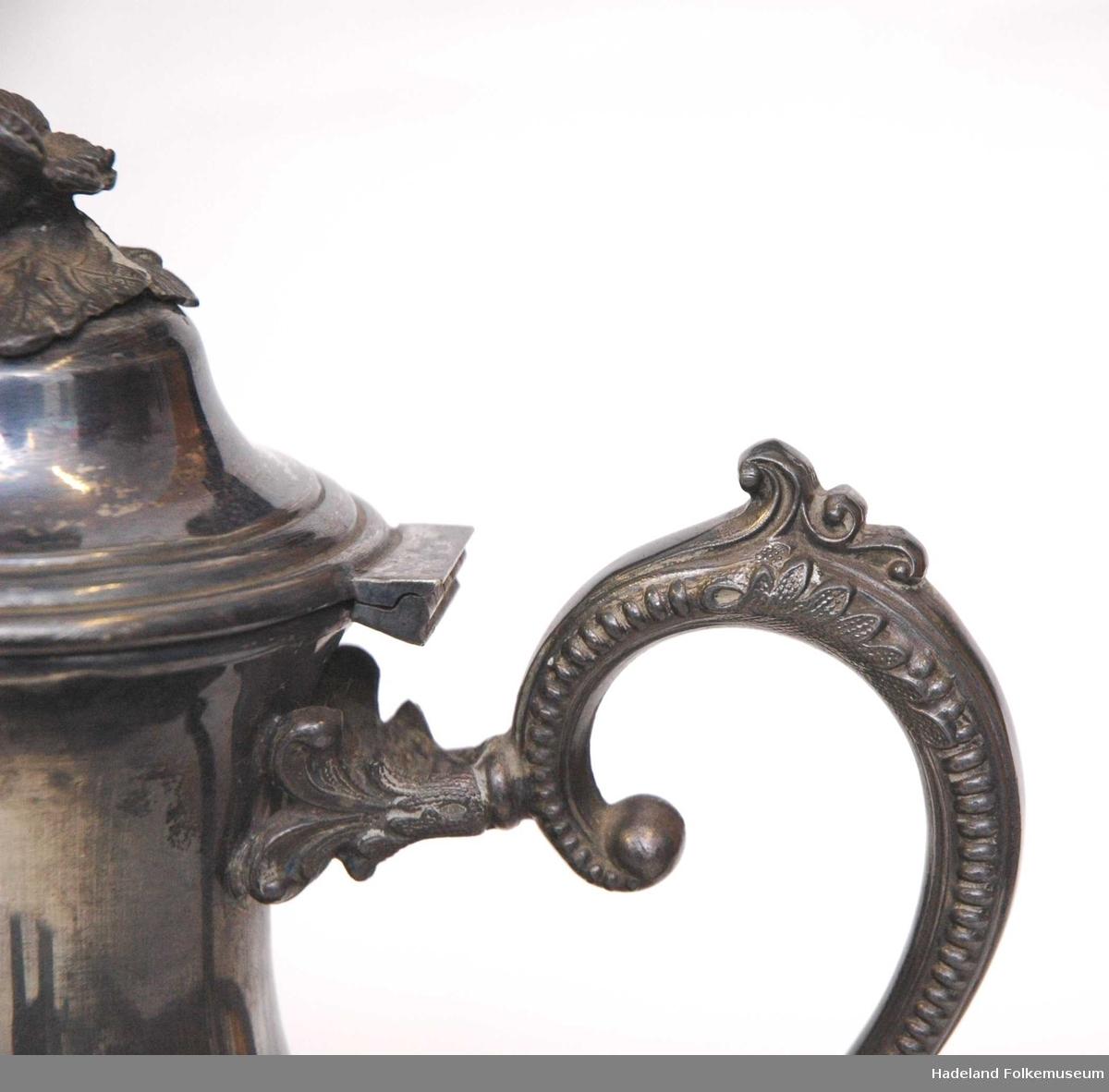 Sukkerkopp(a), Fløtemugge (b) og Kaffekanne (c) i metall. Samtlige deler har fire bein. Dekorert. a) har to hanker til å holde i. b) har hank og tut, c) har hank, tut og hengslet lokk.