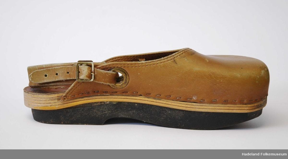Overlær. Festet med reim bak hæl. Spenner på hver side. Skåret tresåle. Pålimt, tykk gummisåle under. Skoen er formet slik at man har hælen lavere en fotballene (negativ hæl).