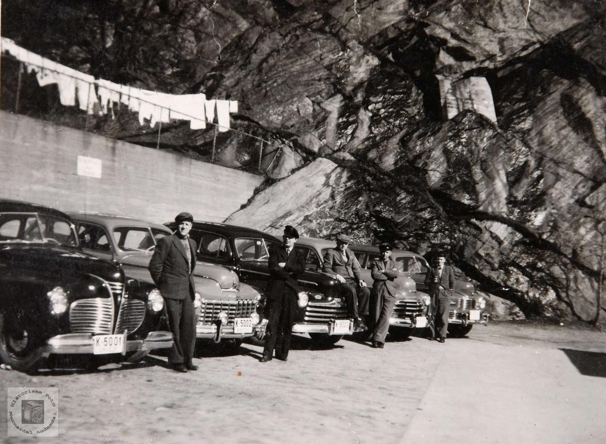 Drosjeparken i Mandal på 1950 tallet. Drosjene fra venstre: K-5001 Plymouth 1940, K-5002 Dodge 1946-48, K-5003 Ford 1946, Chevrolet 1947, Nash 1946-48