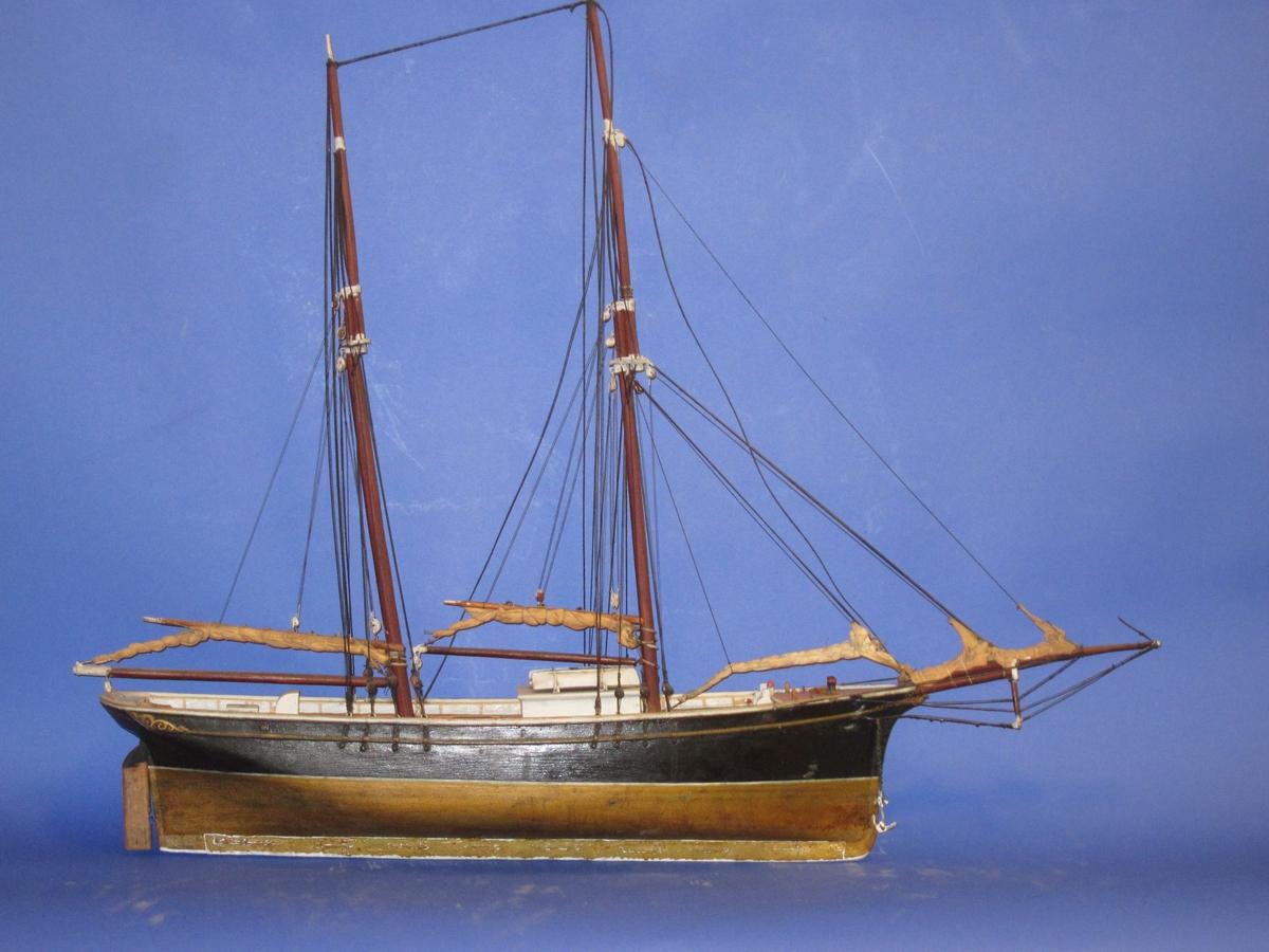 Helmodell  av 2-mastet  slettoppet  skonnert.  Fruktskonnert.  Rigget modell.Beslåtte seil. Sort fribord, bronsefarget undervannsskrog, hvite dekkshus, brune master.