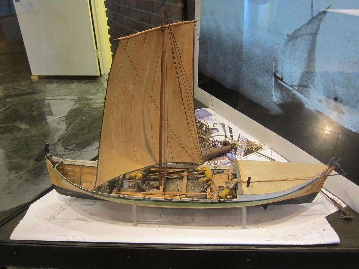 Helmodell av fembøring med 4 mann. Rigget med mast og seil av tre. Diverse inventar registrert for seg.