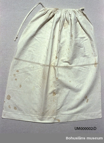 """Vitt förkläde (delvis gulnat) av tyg med bomull i varpen och lin i inslaget, av en rektangulär tygbit, rynkad upptill mot en smal linning. Linningen går utanför tyget en liten bit i höger sida. Där finns ett knapphål. På vänster sida bildar linningens fortsättning en lång knäpptamp som lägges runt midjan baktill och knäpps med en sydd knapp i knapphålet. Ungefär mitt på förklädet, på tvären, finns en ca 1,5 cm bred broderad bård i hålsöm. Enligt Knut Adrian Anderssons katalog I:3:2, D 2 A:1 i museets arkiv, är förklädet del av en kvinnodräkt """"förfärdigad efter äldre personers  beskrivning således efter tradition"""".  Överdel och hätta skänktes av Bertha Kleberg, övriga delar köptes av museet.  Om förklädet står: """"försett med enklaste hålsöm bestämt av en kommitté i Göteborg 1910"""" Detta var den sk Dräktkommittén som man kan läsa om i Ulla Centergrans  C-uppsats (se litt. listan). I gamla kortkatalogen anges att förklädet är kemtvättat 1970. Trots det fullt av bruna fläckar. Knappast slitet.  Litteratur om revitalisering av bygdedräkter på 1900-talet: Arill, David, Bertha Kleberg och Bohusdräkten ur Bohusländska folkminnen Studier och uppteckningar red Arill, David, Uddevalla 1922. Centergran, Ulla, Folkdräktsrörelsen i Bohuslän och Göteborg, C-uppsats i etnologi, Göteborg 1973. Bygdedräkter bruk och brukare, Göteborg 1996.  Wistrand, P G, Bohusländska folkdräkter ur Fataburen häfte 1 1908.  Ur handskrivna katalogen 1957-1958: Kvinnodräkt; fr. Bohuslän a) Kjol, blå. ngt blekt.b) Livstycke, rött m. broderi. c) Överdel, vit m. broderier o hjärt-formad brosch m. furstlig krona. d) Förkläde, vitt. d) Förklädet försett m. enklasta hålsöm.  e) Linnehuva, vit m. spets. Föremålen relativt hela.  Lappkatalog: 76"""