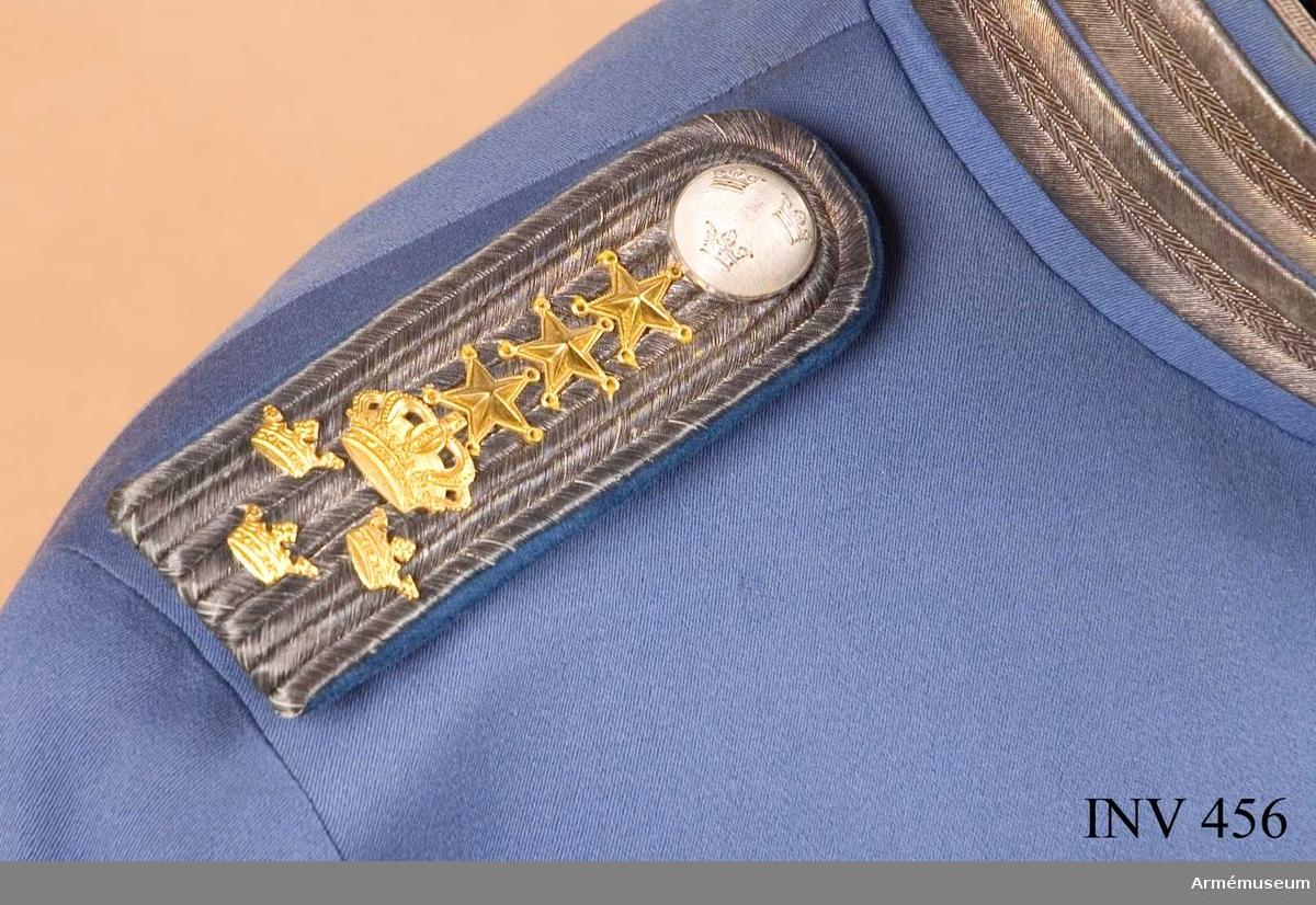 """Styv av silvergalon, fodrad med blått kläde något mörkare än uniformen. Knapp närmast halsen med tre öppna kronor. Silverfärg. Tre guldstjärnor, 15 mm diam, sluten krona, bredd 23 mm, höjd 20 mm, i guld. Därunder tre små öppna kronor, 15 mm breda och 10 mm höga, placerade två över en. På fodersidan metallhake att fästa i uniformen, i gulmetall och märkt """"Milit. Ekp. Akt. Bolag M E A"""". En tamp av fodersidans tyg att fästa med på vapenrocken, 120 mm lång. Klaffen bär gradbeteckning för ryttmästare. Knapp m/1845."""