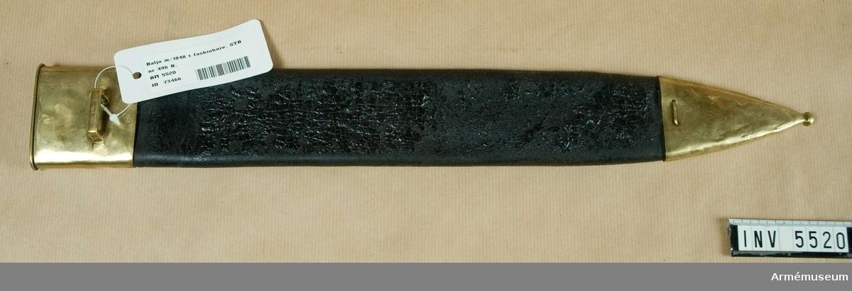 Av svart läder med ca 60 mm högt munbleck och 95 mm hög doppsko av mässing. På det förra en horisontal, platt mässingsbygel för uppkoppling.