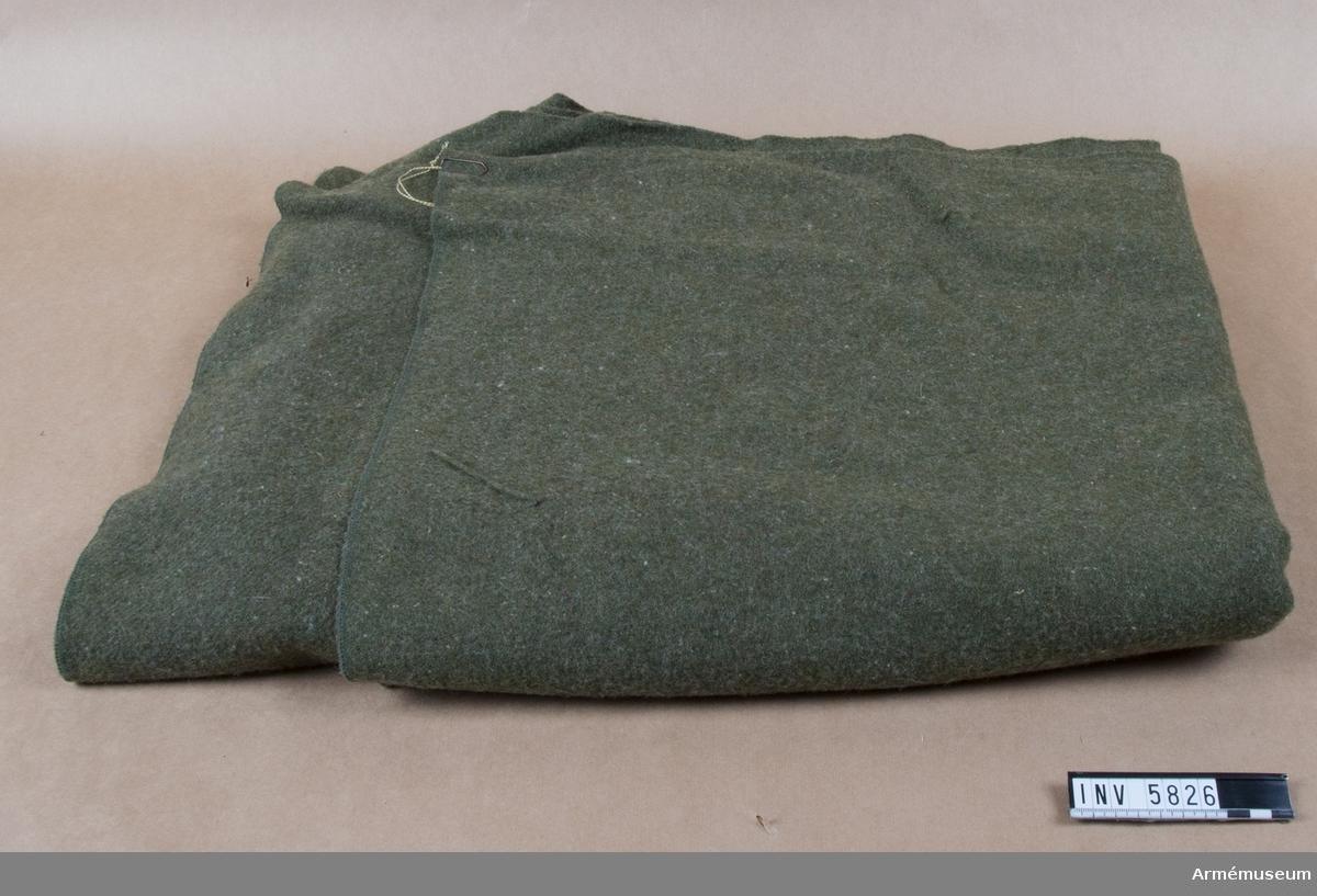Grön sängfilt för FN-bataljonen Mellersta Östern. Filten är på mitten märkt U S. Maskinkastade kanter på kortsidorna./ = radskifte.  Inskription på etikett: '7210-282-7950 / Blanket, Bed, Wool / 65% New Wool / 35%  Reprossed Wool / Mothproofed / Cont. No. Dsa 100-74-F7U599 / F.P.I., Inc.'.
