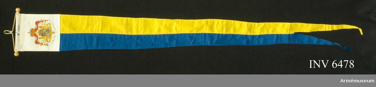 Ett blått och ett gult fält på längden, avsmalnande i två tungor. De blå fältet föres närmast knoppen. Monterad på liten stång m knoppar i ändarna. Stort riksvapen tryckt på båda sidor om ett vitt fält i dubbelt tyg som har mått 200 x 200 mm.  Samhörande nr är AM.6474-6479