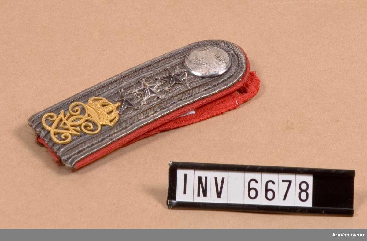 Tämligen gott skick. Mått: längd 120 mm, bredd 40 mm.Försedd med H.M. Konungens namnchiffer i förgylld metall (go 6 juni 1899 nr 675, och 2 april 1908 nr 335). Foder i rött kläde och matta av fem rader silvergalon. Knapp av regementets större modell i silver. Axelhaken märkt: Holts  gulddrageri, Stockholm.