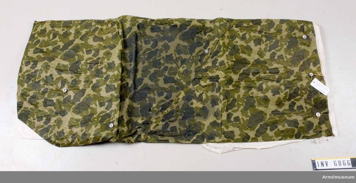 Regnskydd m/1952 m tryckknappar. Färg P Q P. Vikt: 1249,9 gram. Regnskydd, nylon, arbm/1952 utan kapuschong (med tryckknappar). I nylonväv med gummerad baksida. Tillhör KAFI dnr 2937/51 UtrB.