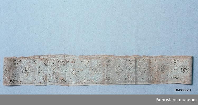 """Broderi med partier av sydd spets. Av en lång dubbelvikt linneremsa (och en liten inskarvad bit) ihopsydd till en sammanhängande räcka. Längs ena kanten uppfållad med hålsöm, längs andra hålsöm men utanför den en traskant (som om remsan suttit fast på ett större tyg där). I spetspartierna utsirade kors i håltagningssöm, där hål har gjorts i tyget och endast ett rutmönster av trådar att sy över har sparats. (Håltagning genom klipp eller utdragna trådar, svårt att ange vilket.) Stygnen i spetskorsen är langettstygn och stopphålsöm. Varje spetskors inramas av en romb sydd med hopdragssöm. Mellan spetspartierna stjärnor sydda i plattsöm. Geometriska mönster sydda i plattsöm, och med små hål insprängda i mönstret, finns även på bottenväven runt spetspartierna. Halva spetskors som utfyllnad längs långsidorna. Troligen stärkt. I Knut Adrian Anderssons första katalogisering I:24:4 står: """"Reticella (lik Hardanger hålsöm)"""". I senare katalog står om tekniken: """"sk Hardanger"""". Broderiet på bottenväven påminner om hardangersöm, men vår tids hardangersöm är grövre. Spetskorsen har snarast karaktären av grovt reticella-broderi. Ursprungligen utfördes reticella i Italien i början av 1500-talet. Pga det trådbundna sömsättet  blev mönsterformerna geometriska. Detta broderi, troligen gjort i Sverige ett par århundraden senare, har ett mönster som påminner om den ursprungliga reticellan. (Jämför bild i Widhja sid. 124, se litt listan) Årtalet 1732 har följt föremålet genom de olika katalogiseringarna på museet. Observera att även UM000067 Broderi är från 1732. Givaren Johanna Selina Eding f. Strandberg f. 1801 d. 1890 var gift med Carl Fredrik Eding f. 1789 d. 1867, överstelöjtnant, sparbanksordförande. Vid deras giftermål förvärvade C.F. Eding det gamla tegelbruket på Elseberg och Elsebergs gård där de bosatte sig. Efter C.F. Eding är Edingsvägen uppkallad. Ytterligare uppgifter om givarens släktförhållanden se UM 64.  Gulnat. Ojämnt mörknat. Många små bristningar och gulbruna fläckar."""