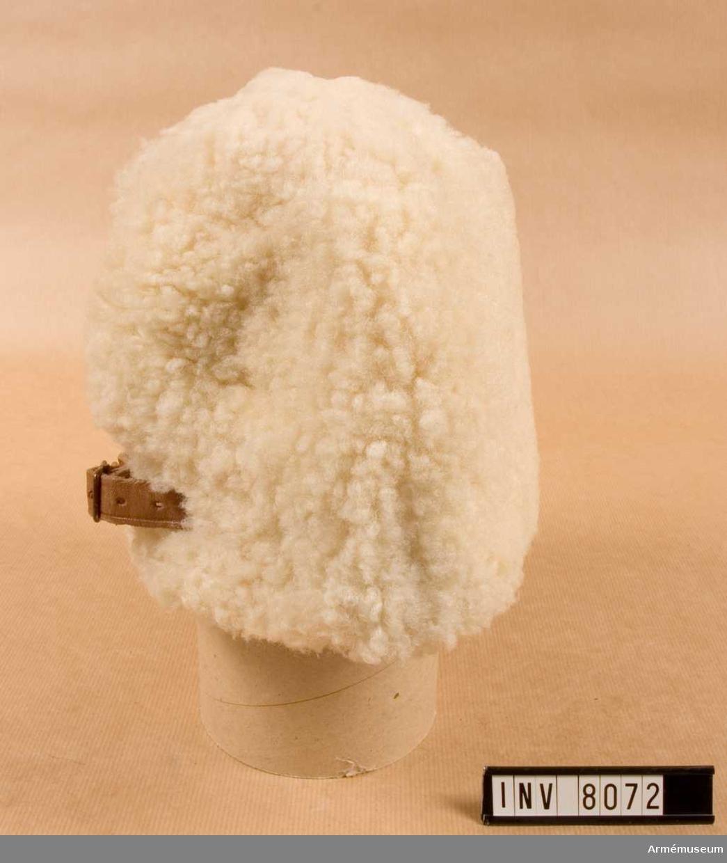 I vitt fårskinn. Höjd 170 mm.  Vidd 610 mm. Vikt 300 g. Fodret är vadderat och har en utvikbar skärm att användas vid behov. Baktill har mössan en rem för reglering av vidden.