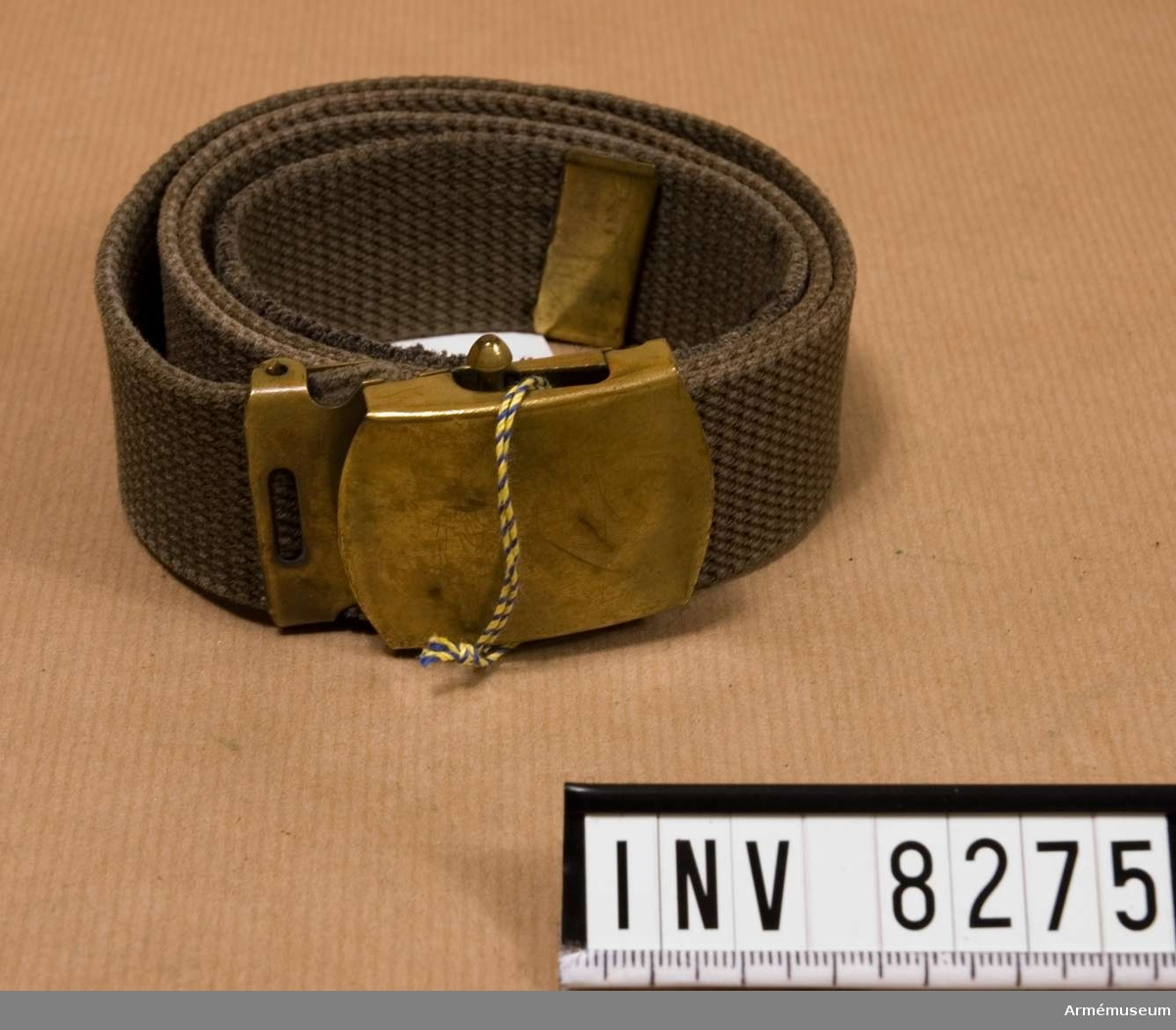Samhörande gåva 8263-8280. Livrem, textil med spänne m/1952. Längd 960 mm. Bredd 35 mm. Vikt 84.1 gr. Färg gröngrå. Gott skick 211. Med gult metallspänne märkt SOLID BRASE.