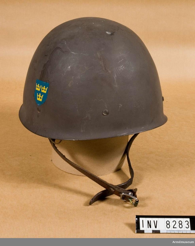 Gråmålad hjälm med en blå sköld med lilla riksvapnet på båda sidor. Inredning i form av tre kuddar, fastnitade i hjälmen. Hakrem av brunt läder. Storlek 69.