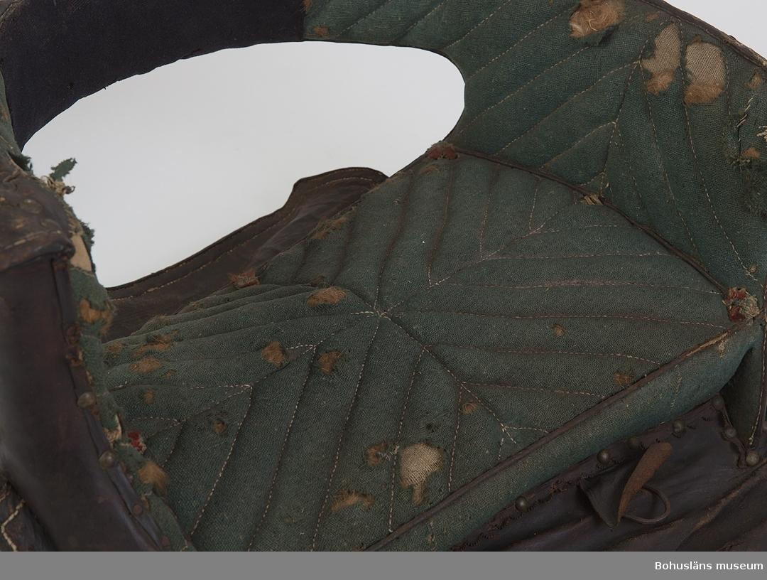 """Tvärsadel av trästomme med vadderad (matelassérad) dyna av mörkgrönt ylletyg. Dynan har ett sytt randmönster med naturfärgad tråd. Stoppning av bl. a. djurfibrer. Sex (nio i original) tofsar i blått, rött och vitt fördelade i dynans hörn.Vadderingen fortsätter på armstödets insida. Sekundärt lagat med mörkblått tyg. Utsidan är klädd med präglat läder. Dubbla sidostycken av läder med smidda ringar för att fästa stigbygeln. Remmar att spänna åt sadeln med. Sömmarna är defekta. Putor av naturfärgad väv med stoppning av halm. Stoppningen hänger ut ur kanterna fram- och baktill. Ylletyget är rejält skadedjursangripet samt blekt. Stigbygel saknas.  Litteratur: Ur årsboken """"Kulturen 1957"""", Brudsadel 1900, s. 42-43.  Ur handskrivna katalogen 1957-1958: Damsadel L. 56; Br. c:a 50 cm. dyna och ryggstöd klätt m. grönt ylletyg; lädret delvis dekorerat; stoppn. på undersid. trasig (hö); mask, malhål.  Lappkatalog: 40"""