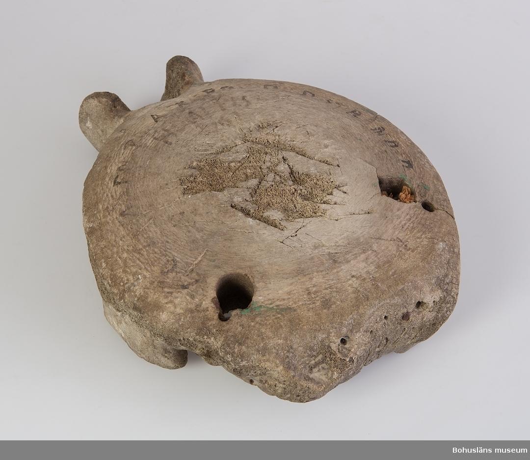 """Ur handskrivna katalogen 1957-1958: Kotkropp av jätteval.  Ryggkota av val omgjord till stolsits. Tre hål för stolsben, rester av trä finns kvar i ett av hålen. Två av hålen borrade, ett är naturligt. Ovanpå """"sitsen"""" står skrivet: """"Denna stol gjorts av en på Askeröd strandad hvalfisk 1767""""."""