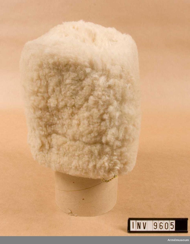 Av vitt fårskinn. Ljusbrun rem i nacken för reglering av  mössvidden. Fodrad med ett grått bomullstyg som är vadderat. I pannan finns en skärm av grått läder som är invikbar mellan foder och mössa.