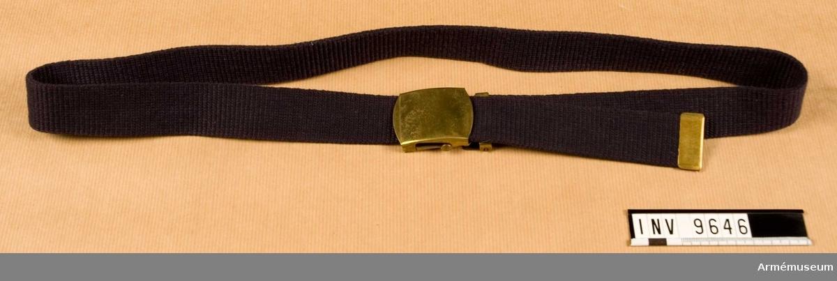 """Byxbälte m/1948, flottan. Ett vävt bomullsband i mörkblå cordbindning, skämtsamt kallat """"fläktrem"""". Försett med spänne och ändbeslag i mässing. Källa: Uni FL nr 806."""