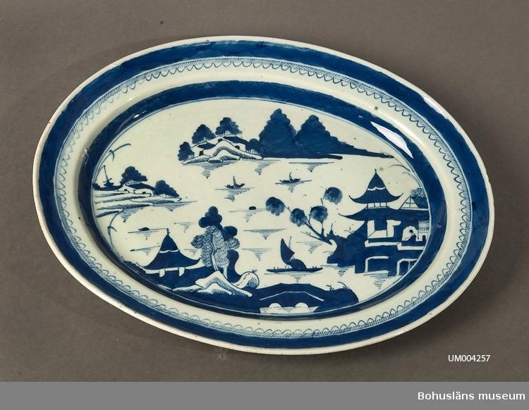 Ur handskrivna katalogen 1957-1958: Porslinsfat fr. Ostindien L. 42,3 Br. 33,7. (ovalt). Vitt porslin med blått mönster (landskap). Mycket obetydlig kantskada.  Lappkatalog: 62