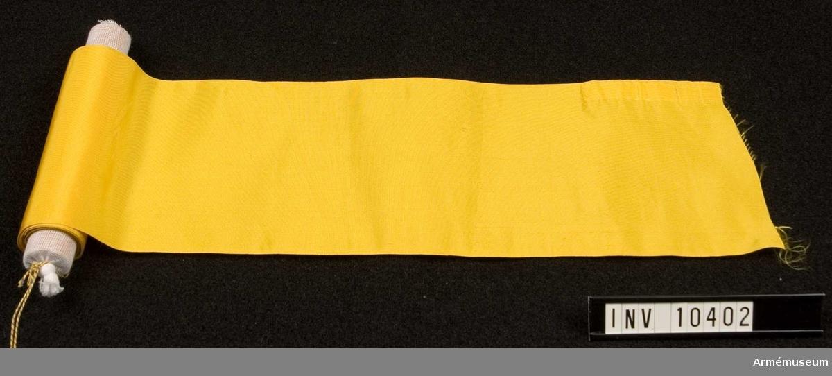 Grupp B I. Fanband m/1899, gula. Deponerad från Arméförvaltningens Intendenturdepartemente, modellkammaren. Enligt AM nämnd beslut 195211 överlämnat till K.A.F.I., Utrustningsbyrån, 63,5 m (63500 mm).