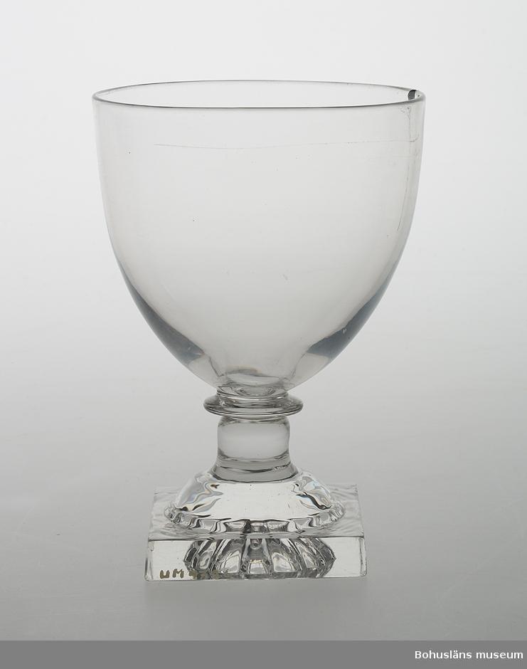 Ur handskrivna katalogen 1957-1958: Dricksglas 13 cm. spräckt Mynningsdiamet.: 9,1 cm Fotplattans mått: 6,2 x 6,1 cm. Vitt glas. En spricka i skålen. För övrigt helt.