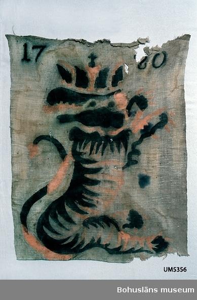 """Textil av oblekt, tuskaftvävt linnetyg. Med schablonmålad bild av heraldiskt lejon med krona på huvudet i svart och rödgult (orange) samt årtalet """"1780"""" i svart. Nertill fållad. Jaktlappar användes vid sk drev- och skalljakt för att avgränsa jaktplatsen och för att skrämma villebråd, mest älg och rovdjur som varg och björn. Upp till 60 meter långa rep med jaktlappar finns på länsmuseet i Skara. De har varit använda vid det kungliga hovets jakter under 1800-talet i Edsmärens kronopark i Västergötland. Jaktlappens proveniens är okänd. Jfr UM020967 Jaktlapp med samma motiv från Halle-/Hunneberg, Västergötland. Trasig upptill och nertill. Fläckig. Färgen bitvis """"utsmetad"""". Blekt.  Ur handskrivna katalogen 1957-1958: Skrämselduk 1780 def. Mått c:a 80 x 60 cm. Målning på gråbeige duk. """"Odjur"""" i rött o svart, som gör krumsprång. """"1780"""". Illa medfaren. Trasig."""
