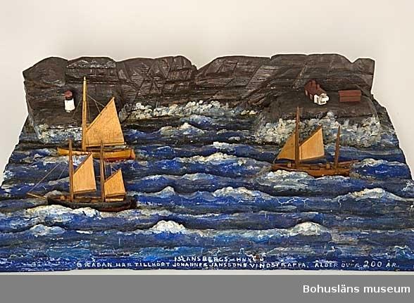 """Modell över Islandsbergs huvud med fyrplats och tre segelfartyg tillverkad av kapten John Emil Olsson (1880-1950), Fiskebäckskil på Skaftö i Lysekils kommun 1943. Trä, lintråd, gips, målat med oljefärg. Fartygsmodeller höjd 10 cm, längd 9 - 11 cm, bredd 2 cm, platta 43,5 x 27 x 8 cm.   Blockmodell av två kuttrar och en galeas under segel i hård västlig vind. Målade och lackade. Stående och löpande rigg och segel av snidat trä.  Monterade på en rektangulär träplatta med modellerat och målat gipshav mot en bakgrund av bergvägg och klippa skuret i trä. På klippan ett hus målat i rött med vit gavel, en röd fyrbod samt vit- och rödmålad fyr närmare vattnet. Framtill på plattans långsida står textat med vita tryckbokstäver:  ISLANSBERGS-HUVUD BRÄDAN HAR TILLHÖRT JOHANNES JANSSONS VINDSTRAPPA. ÅLDER ÖVER 200 ÅR 1943.  Islandsberg längst ut på Skaftölandet i mellersta Bohuslän är en av kustens mer fruktade passager. Här växer sig sjön hög vid hård västlig och sydvästlig vind och suger tag då den slår rakt in mot den 35 meter höga klippväggen som stupar ytterligare 30 meter lodrätt ner mot havsbottnen. Ytterst på klippan, Torskepallen, ligger Islandsbergs gamla fyrplats, ett kombinerat fyr- och bostadshus som från 1883 vägledde sjöfarare med varnande blink. 1938 ersattes fyren av en automatiserad fyr, strax norr om den gamla. Se fotografi Islandsbergs fyr den 10 oktober 1910, UMFA53278:875   Ur handskrivna katalogen 1957-1958: Islandsbergs huvud Modell på platta av fyr och tre båtar. Föremålet helt. Plattans mått: 44 x 27. Från kapten Olssons saml., Fiskebäckskil.  För ytterligare information om John Emil Olsson och förvärvet, se UM005807.  Föremålet presenterat på Bohusläns museums hemsida år 2009 - 2013, webbutställning """"John Emil Olsson Fiskebäckskils sjöfartsmuseum""""."""