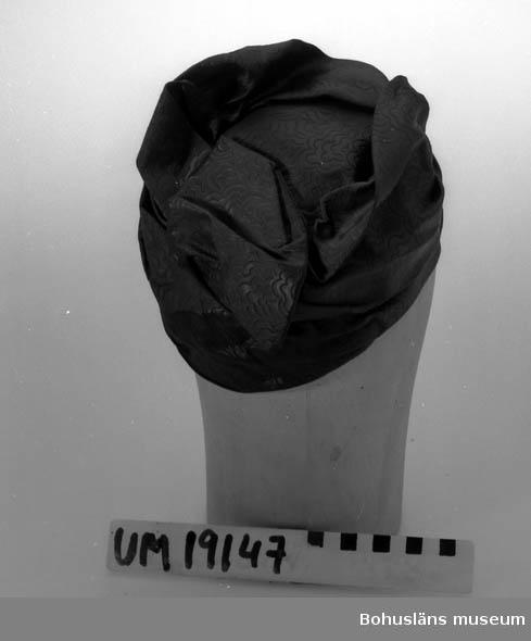 471 Tillverkningstid 1930-TAL 394 Landskap BOHUSLÄN  Damhatt i tryckt svart tyg med veck upptill.   Se UM19130.