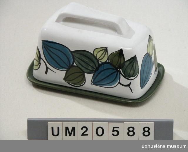 """Grönglaserad platta märkt i botten med signatur i relief: """"SYCO - Sweden 4034 """" Vitglaserad kupa med handmålad dekor av löv i blått, grönt, gult och svart.  Handtag. Märkt med påklistrad firmaetikett. Även insidan vitglaserad."""
