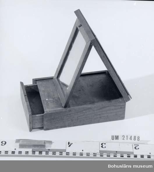 594 Landskap BOHUSLÄN  Raklådan innehåller spegel och en liten draglåda. Locket sitter fast med två mässinggångjärn i ena ändan av lådan. Ett lås finns,nyckel saknas. Spegeln fälls fram då man öppnar locket. Lådan är sprucken.  UMFF 26:1