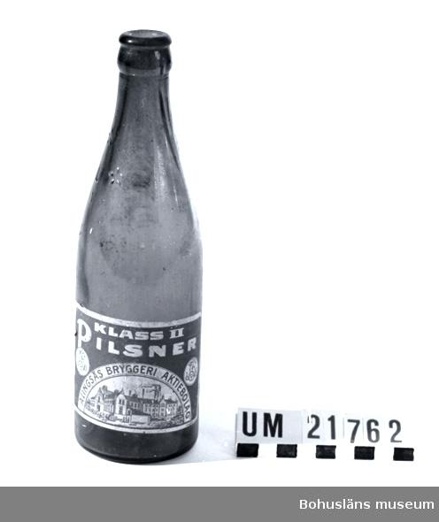 """594 Landskap BOHUSLÄN 394 Landskap VÄSTERGÖTLAND 010 Mått: Diam 2,7 cm.   Flaskan av brunt glas med alkamynningsknopp,  det ringformade  urtaget på flaskknoppens utsida. för  """"Alka-förslutning"""" i aluminium. Etikett i vitt och blått med text: """"Klass 2 Pilsner Alingsås Bryggeri Aktiebolaget"""", samt """"Skånskt lito AB"""". Alka-förslutningen är ett svenskt patent  av A. J. Jonsson, Linköping introducerad efter 1930. Ölflaskan är Sveriges andra standardiserade bruksföremål, d v s ett föremål med i landet överenskomna mått oavsett tillverkare.  Sveriges första """"standard"""" är tändsticksasken.  UMFF 49:6.  Liandergårdens Glasmuseum drivs av Limmareds hembygdsförening och  glasbrukets historia presenteras på deras hemsida.  Litt: Fogelberg, T., Nisbeth Å.: Värmländska glasbruk. 2, Liljedals glasbruk / Värmlands museum 1979. Småskrifter utgivna av Värmlands museum. Förpackningar. Kulturen 1987, Årsbok för Kulturen i Lund. Glasfolket. Buteljglasbruket i Hammar 1854-1930 . Örebro, Morgonstjärnan. Del I 1991, Del II 1994. Hermelin, C. F., Welander, E.: Glasboken. Historia, teknik och form. Askild & Kärnekull 1980."""