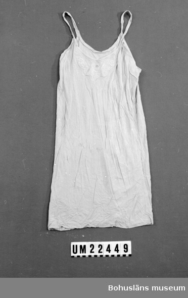594 Landskap BOHUSLÄN  Underklänningen är av ljusblått silketyg med smala axelband. En broderad ros av vitt silkegarn på bröstet, underklänningen är delvis blekt.  UMFF 109:3