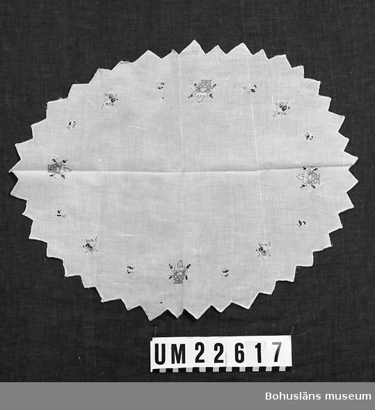594 Landskap BOHUSLÄN  Ljusröd oval duk med triangelformad uddkant. Broderade blomsterkorgar och små buketter med silkegarn i färgerna brunt, lila, svart, gult och grönt.  UMFF 123:4