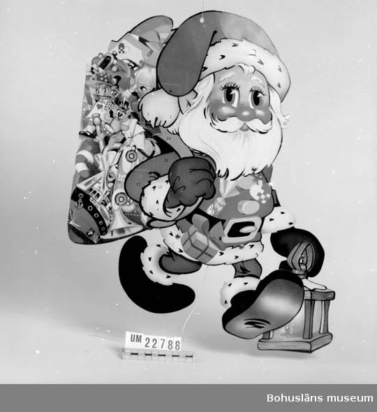 571 Användningstid JULEN 1986  Tomte med numrerad kalendersäck. Snöre och snoddar på baksidan. Ben och armar rörliga. Neg.UMFF 139:11