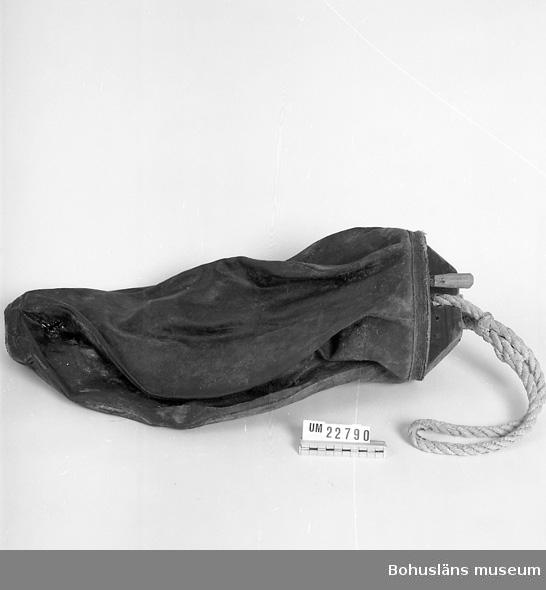 Använd vid fiske. Segeldukspåse med botten av trä. I botten är det en tvärslå med ett rep samt ett hål med en plugg. Segelduken är impregnerad med tjära för att vara vattentät. Påsen är ihop tryckt och stel.  Ingår i redskapsbestånd ur sjöbod från Hällsö, Havstenssund, Tanum sn. Se UM 17521