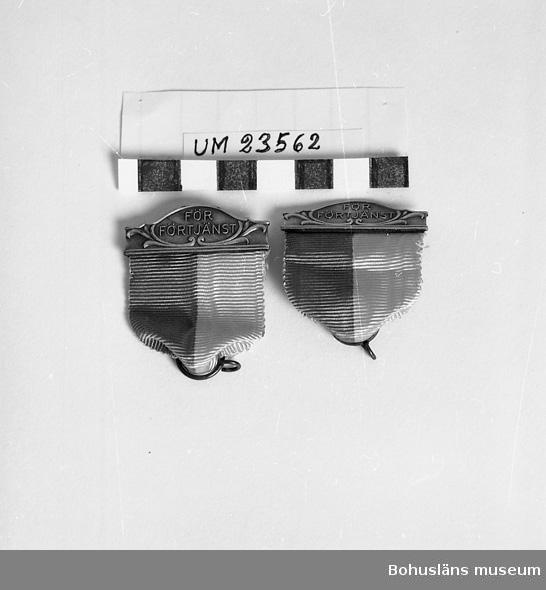 """471 Tillverkningstid 1950-1960 594 Landskap BOHUSLÄN  Blått med gult band med ögla nedtill för medalj. Upptill skena i silver med texten: """"För förtjänst"""" i kartusch. På baksidan nål. För silvermedalj. Jfr UM23561 och UM23563. Förvarades i ask UM23560."""