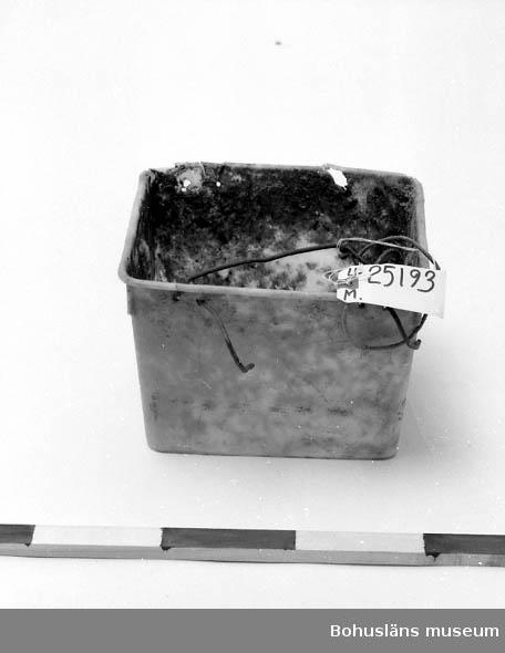 594 Landskap BOHUSLÄN 503 Kön MAN  Vit-grå. Fyrkantig. På ena långsidan är det en metalltråd för upphängning.  I metalltråden är ett snöre av textil knutet. Smutsig av lera och av rester av agn. Använd vid burfiske efter havskräfta. Inventerat 1996-07-23 GH.