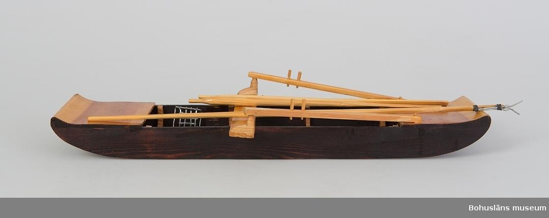 Modell av stockeka tillverkad av givaren efter originalbåt från Överby och Stora Holma, Strömstad.  Svartmålat srov i rektangulär form med årställning och lösa tilbehör: två lösa åror, L 26 cm;  ljuster på stång, L 42 cm ; blosskorg H 7 cm och öskar L 3 x cm B 1,2 cm.