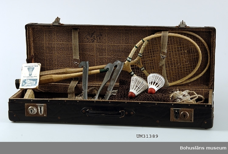Badmintonrack av märket Ideal av klarlackat trä med nät av sena. Gröna detaljer. Handtaget  ytterst förstärkt med svart skinnremsa. Detta är det en av två likadana racketar i badmintonväska UM31389:1. Möjligen är dessa racketar en senare komplettering och har inte från början hört till utrustningen i väskan.  Badminton spelades på tomten och nätet spändes upp mellan två tallar. Det hände ofta att fjäderbollarna fastnade i grenverket. Dessa fick man försöka dra ner med krattor. De medföljande badmintonbollarna är senare komplement. De ursprungliga hade en gummibotten samt vita fjädrar. Se fotografi UMFA55058:0014.  Föremålet har använts av familjen Abrahamson i deras sommarstuga i Sundsandvik, byggd 1939. För ytterligare upplysningar om förvärvet, se UM031385.