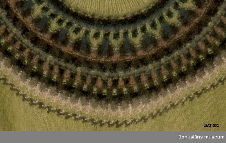 Jumper med lång ärm stickad i ejagarn och angoragarn. Rund halsringning. Fem cm öppning på bakstycket uppe vid nacken vilken justeras med dragkedja. Mönsterstickat rundstickat ok i olika nyanser av brunt och beige. Grundmönstret heter Tobak, angoraull i nio nyanser av brunt och beige komponerat av Annika Malmström-Bladini 1957. I detta plagg har emellertid nyansen grönt använts som bottenfärg. Grönt ingår även i oket. Några av okets originalfärger har utgått.