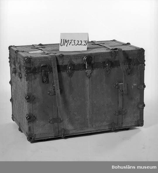 Koffert på hjul. Papp klädd med rikligt med mässingfärgade gjutna beslag. Läderhandtag med instansade siffror (36 086). På ena gaveln stämplade bokstäver: R.E.  Ur punktnummerkatalogen 1958-1976: Köpm. Georg Jansson, U:a Amerikakoffert