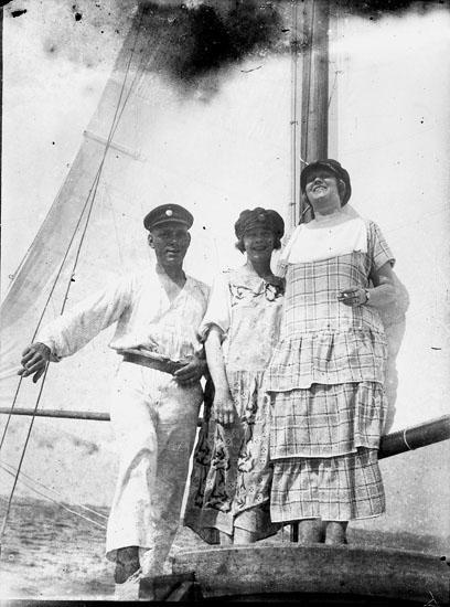 """Enl. text i blå bok: """"Man och två damer vid mast på en segelbåt."""" ::"""