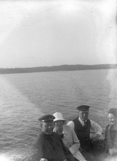 "Enl. text i blå bok: ""Personer i sittbrunnen på båt."" ::"