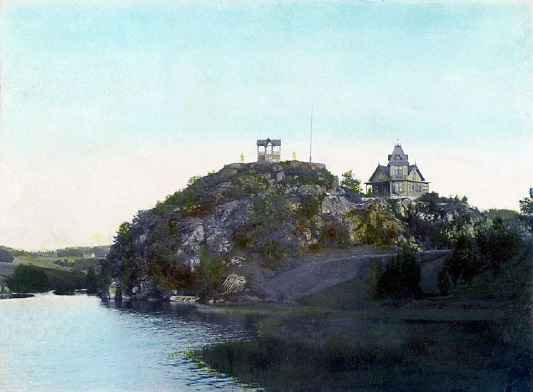 Handkolorerat fotografi över Villa Älvkullen med dess lusthus på ett berg vid Bäveån, Uddevalla. Från 1900-talets början.