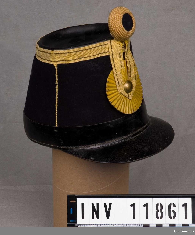 Grupp C I. Huvudbonad s k käppi m/1858 tillverkad av mörkblått kläde med svart lackskärm och lack under nedre delen av kullen, 3,5 cm högt. Gulmålad läderkokard, veckad, diameter 8 cm med en slät kupad knapp i mitten, hållande en stolpe av gult redgarn med blå dekorationsband vid sidorna. Det gula redgarnet går även runt kullens övre del. Kullen är av svart läder. Mitt fram hål för pompongen. Invändigt skodd med svart läder som är tillskuret i flikar med hål i topparna med möjlighet att dra i ett band  för att reglera kullens höjd (storleken) för bäraren. Hakrem av svart läder.
