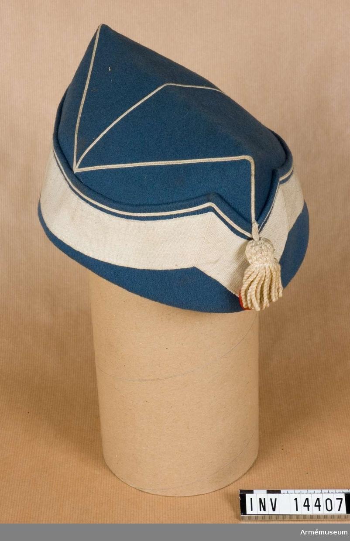 """Grupp C I. 1940. Av ljusblå kläde, båtmodell. Kantad m vitt bomullsband, b:35 mm, och passpoal. På framsidan en vit tofs och den ovala, danska nationalkokarden av vitt-rött tyg =nationalfärger. Foder av grått tyg m stämplar """"19 M 1 40"""" =Munitionsdepot N 1, """"Lg"""" =Livgardet. LITT  Armeen Album I. Die Daenische Armee, Leipzig. Verlag von M Ruhl. Sida 7-8. Leibregiment. """"Livgarden"""" t fält och """"kleinen Anzug"""" ljusblå mössa m vit galon, passpoal och tofs. Bil. sida 1-2: gardister m mössor liknande denna.Enl Granberg 1951."""